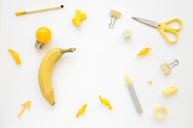 Plátano, bombilla eléctrica, caramelos y papelería sobre fondo blanco