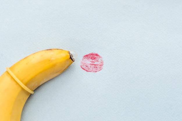 Plátano en un condón y una huella de labios rojos. concepto de sexo oral.