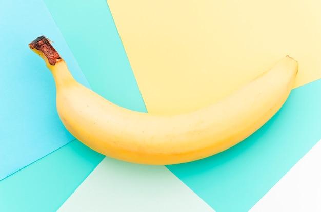 Plátano curvo amarillo sobre superficie multicolor.