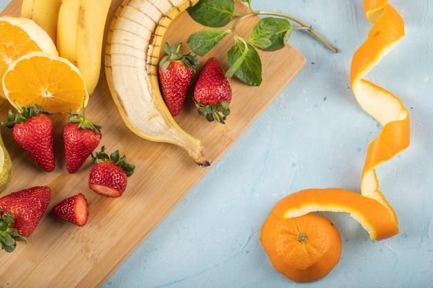 Plátano fresco, naranja y fresas en una pared azul con hojas de menta