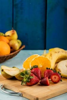 Plátano fresco, naranja y fresas en un tablero azul