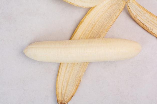 Plátano pelado solo sobre mesa blanca
