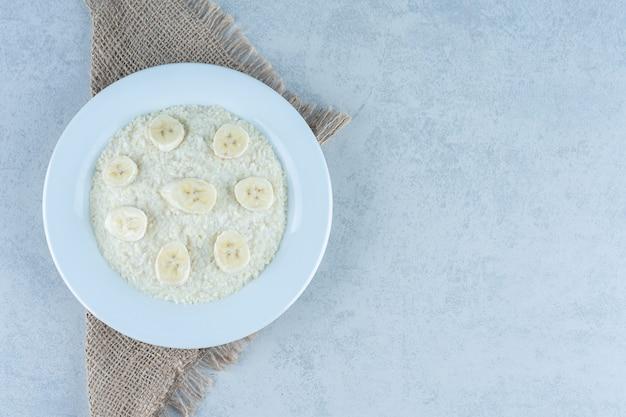 Plátano en rodajas en un plato de arroz sobre mármol.