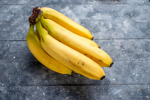Plátanos amarillos frescos bayas enteras sobre gris, sabor a vitamina baya de fruta