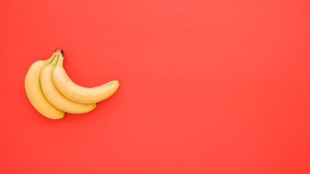 Plátanos amarillos sobre fondo rojo con espacio de copia para escribir el texto