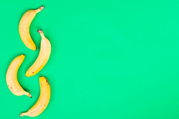 Plátanos amarillos sobre fondo verde