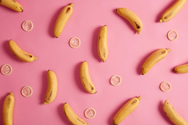 Plátanos y anticonceptivos sobre fondo rosa. condón de sabor tropical para una relación segura. eliminación del riesgo de embarazo. proveedor de atención sanitaria. condón probado para resistencia, flexibilidad y confiabilidad.