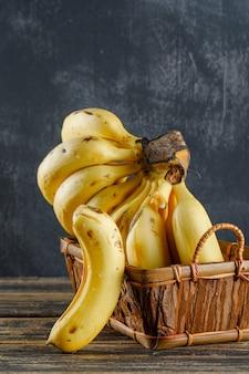 Plátanos en una canasta sobre madera y yeso.