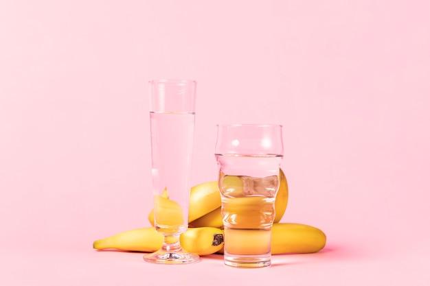 Plátanos y variedad de vasos con agua.