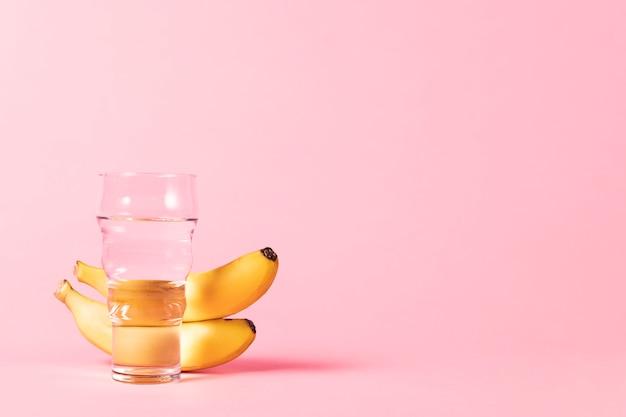 Plátanos y vaso de agua copia espacio