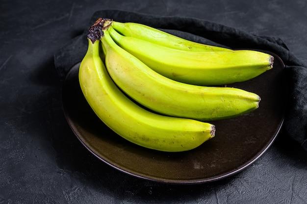 Plátanos verdes en un plato. fondo.