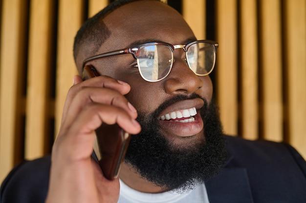 Plática de negocios. un hombre de negocios de piel oscura hablando por teléfono y mirando involucrado