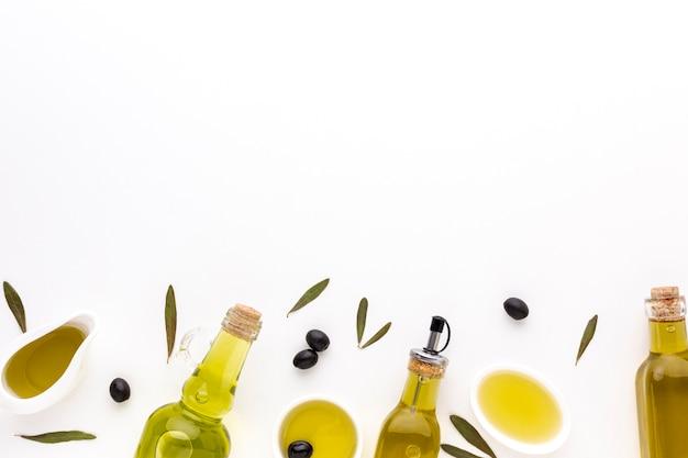 Platillos y botellas de aceite de oliva con espacio de copia