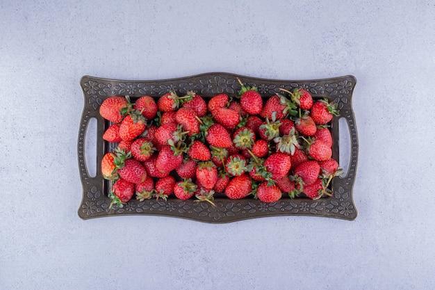 Plato adornado de jugosas fresas sobre fondo de mármol. foto de alta calidad