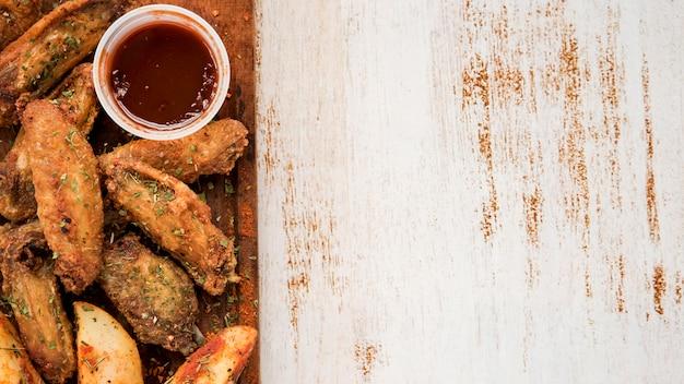 Plato de alas asadas con patata y salsa.