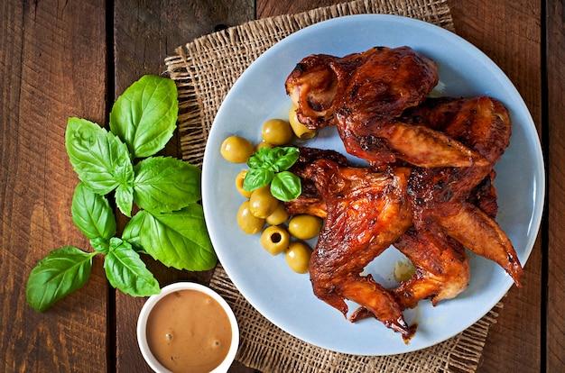 Plato de alitas de pollo en la mesa de madera