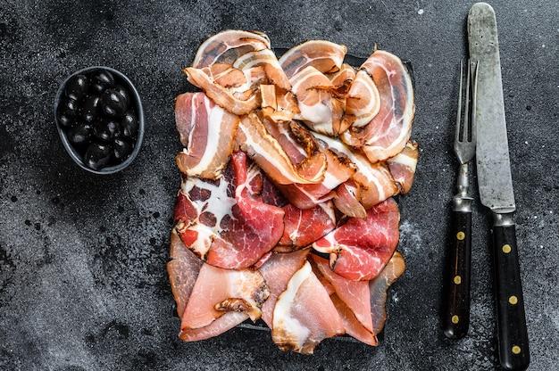 Plato de antipasto de carne, panceta, salami, lonchas de jamón, salchicha, prosciutto, tocino. fondo negro. vista superior.