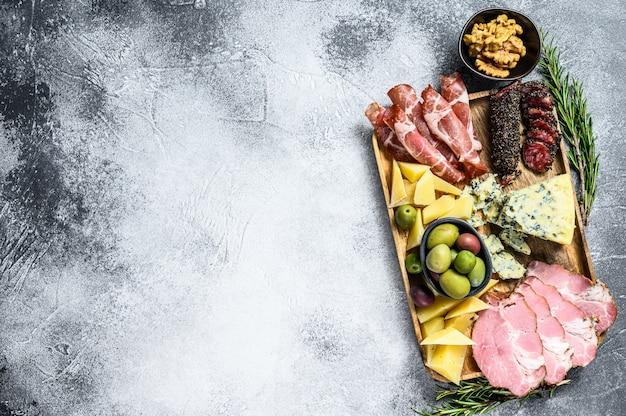 Plato de antipasto con jamón, jamón serrano, salami, queso azul, mozzarella y aceitunas. vista superior. fondo copyspace
