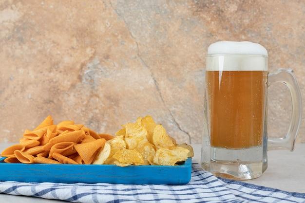 Plato de aperitivo y vaso de cerveza en el mantel