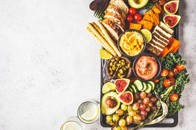 Plato de aperitivo vegano, hummus, tofu, verduras, frutas y pan.
