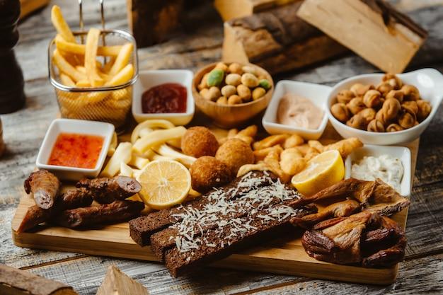Plato de aperitivos con alas ahumadas salchichas papas fritas nueces y salsas
