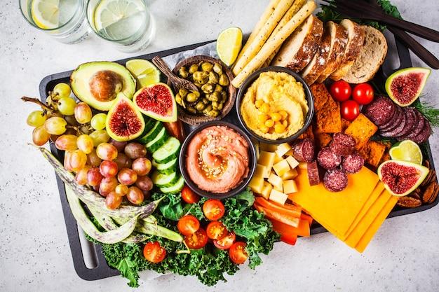 Plato de aperitivos de carne y queso. salchichas, queso, hummus, verduras, frutas y pan.