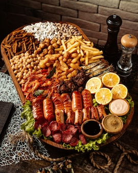 Plato de aperitivos de cerveza con camarones salchichas garbanzos queso frito papas fritas semillas de girasol y limón