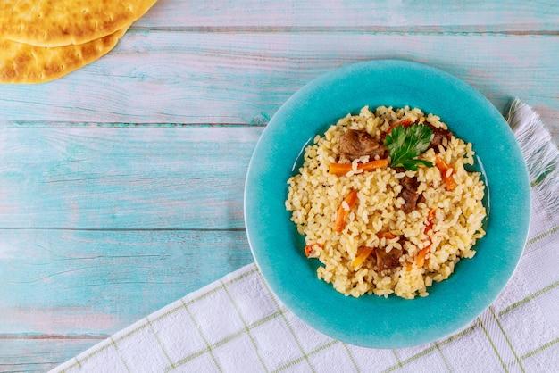 Plato árabe con arroz, carne, zanahoria y pan de pita.