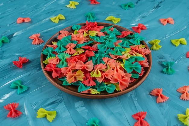 Plato de arcilla de pasta farfalle cruda colorida sobre fondo azul.
