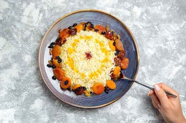 Plato de arroz cocido shakh plov de vista superior con pasas dentro de la placa en el espacio en blanco