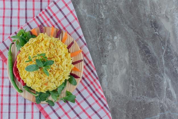 Plato de arroz integral cocido sobre una toalla doblada, adornado con pimiento, hojas de menta, zanahorias en rodajas y remolacha sobre mármol.