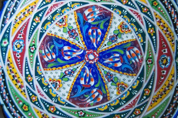 Plato autentico de ceramica con patron arabesque abstracto.