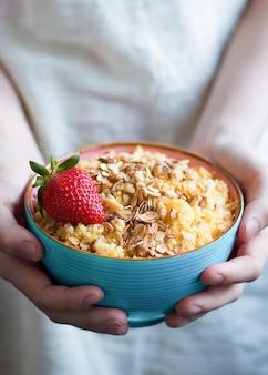 Plato azul de gachas de maíz con granola y fresa en manos de una niña vegana dieta saludable