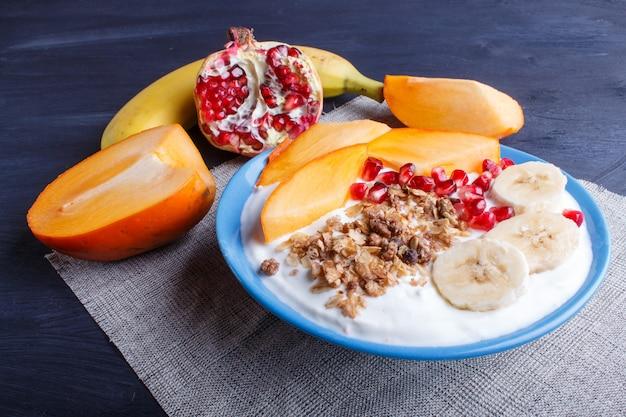 Un plato azul con yogur griego, granola, caqui, plátano, granada.