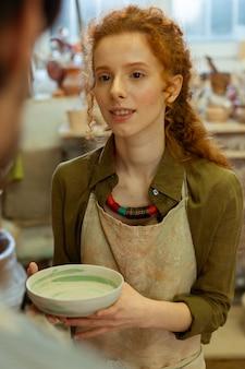 Plato de barro pintado. sonriente niña de pelo largo presentando plato de barro hecho a mano a su maestro durante la clase magistral de cerámica