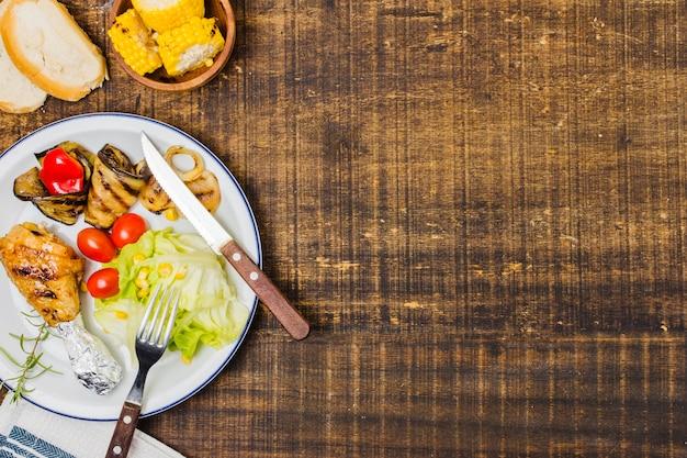 Plato con bbq de verduras crudas y pan.