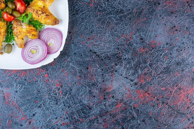 Plato blanco de alitas de pollo a la plancha con verduras orgánicas en la superficie de mármol.