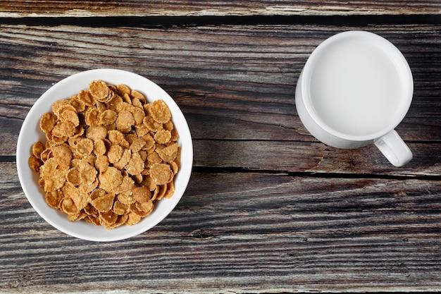 Plato blanco con cereal saludable desayuno y taza de leche