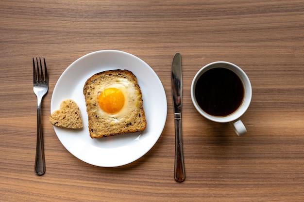 Plato blanco con corazones de pan, pan horneado y huevo y taza de café con leche.