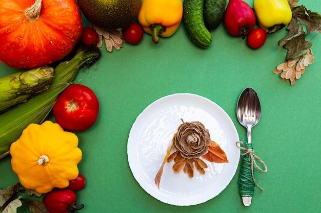 Plato blanco y cubiertos en hojas de otoño y verduras