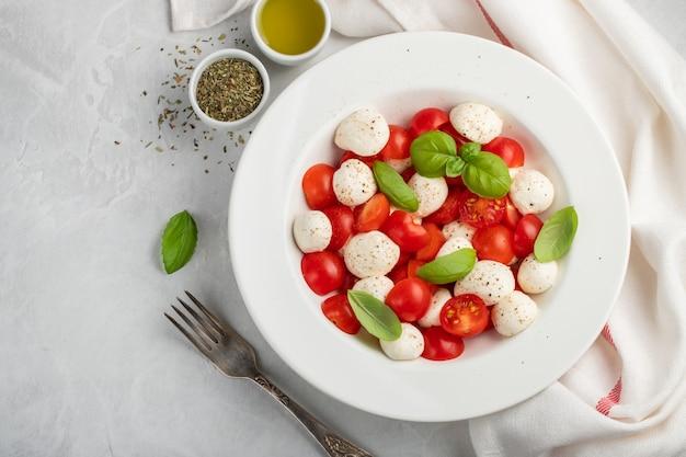 Plato blanco de deliciosa ensalada caprese clásica.