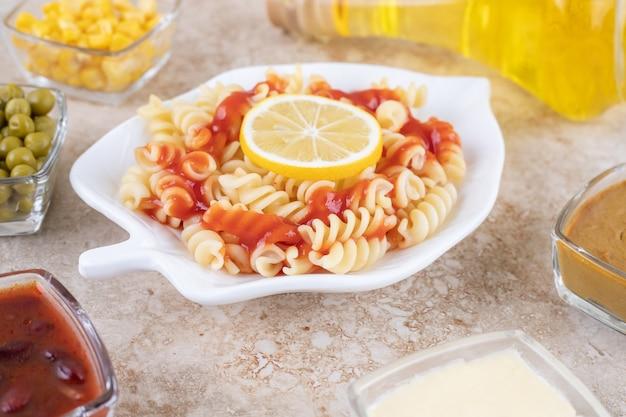 Un plato blanco de deliciosa pasta espiral con rodaja de limón