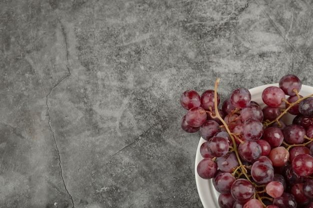 Plato blanco y deliciosas uvas rojas sobre mesa de mármol.