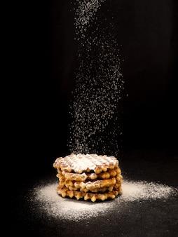Plato blanco con gofres belgas caseros, encima de tamizado vertido de azúcar en polvo en un bocadillo negro muy sabroso. azúcar sobre mesa de madera vieja. estilo rústico oscuro.