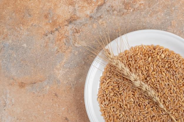 Un plato blanco de granos y trigo sobre fondo de mármol. foto de alta calidad
