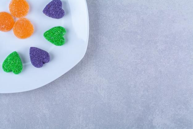 Un plato blanco lleno de caramelos de gelatina azucarada sobre fondo gris. foto de alta calidad