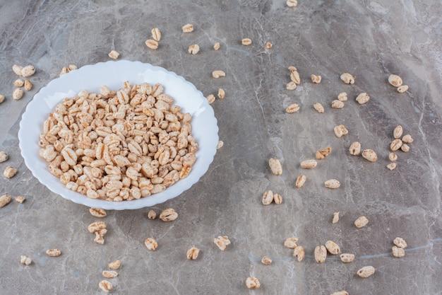 Un plato blanco lleno de cereal de desayuno de arroz crujiente.