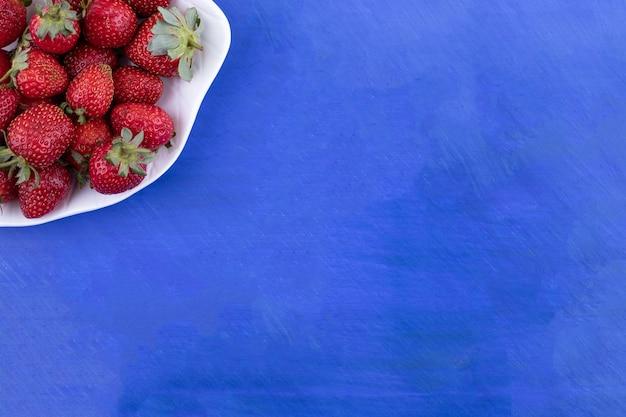 Un plato blanco lleno de fresas sobre superficie azul