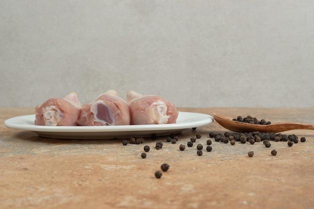 Un plato blanco con muslo de pollo crudo con cuchara de madera de pimienta