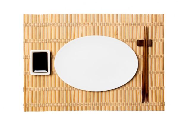Plato blanco oval vacío con palillos para sushi y salsa de soja sobre estera de bambú amarillo.